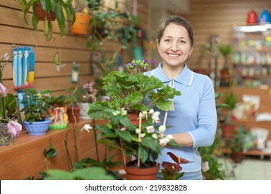 Happy mature woman holds primrose surrounded by different flowers in store