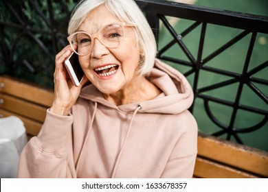 Happy mature woman in hoody and stylish glasses is talking on smartphone in park