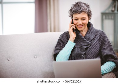 Happy mature woman with laptop using mobile phone while sitting on sofa at home