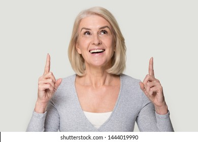 Happy mature woman look up showing up with fingers portrait. Head shot of smiling elderly female holding finger up isolated on grey. Attract attention, share good news, invite, offer to see something