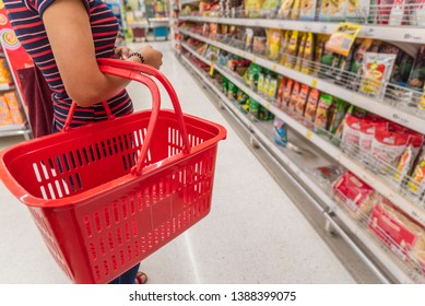 Happy mature woman looking at camera while shopping in grocery store. Casual woman choosing food from shelf in supermarket and looking at camera. Smiling customer standing near shelves.