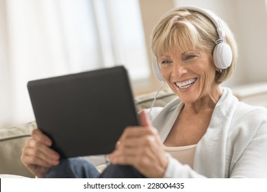 Happy mature woman looking at digital tablet while using headphones at home