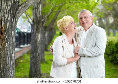 Happy mature woman looking at her husband while having rest outside