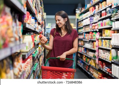 Happy mature woman looking at product at grocery store. Smiling hispanic woman shopping in supermarket and reading product information. Costumer buying food at the market.