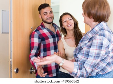 Happy mature woman meeting  young couple at the door