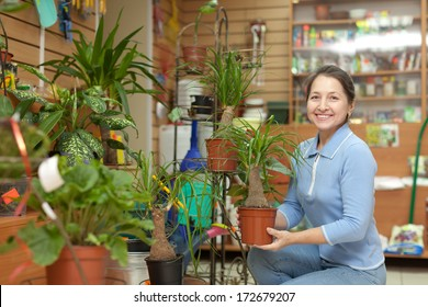 Happy mature woman with Nolina plant surrounded by different flowers in flower store