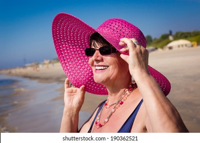 Happy mature woman on the beach. Selective focus.