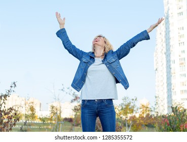 Happy mature woman on the blue sky background. Beautiful adult woman enjoying and happy - freedom concept. Second youth.