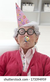 happy mature woman with party hat and noise maker