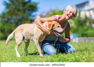 happy mature woman plays with a Labrador retriever dog outside