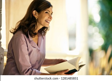Happy mature woman reading her book on the porch.