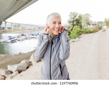 Happy Mature Woman Relax Listening Music With Earphones After Jogging, Gray-Short Hair, Wear Sports clothes ,Workout Outdoor.