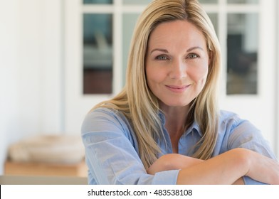 Happy mature woman relaxing on her couch at home in the living room. Close up face of senior woman looking at camera. Portrait of happy woman in blue shirt smiling.