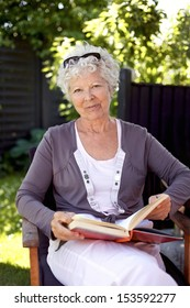 Happy mature woman sitting on a chair in garden with a book looking at camera smiling - Elder woman reading outdoors