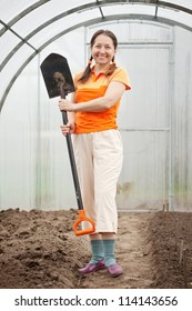 Happy mature  woman  with  spade in hothouse