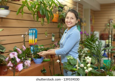 Happy mature woman  surrounded by different flowers in flower store