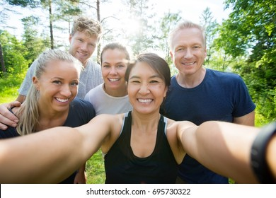 Happy Mature Woman Taking Selfie With Friends In Forest