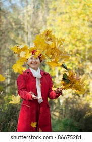 Happy mature woman throwing yellow maple leaves  in autumn