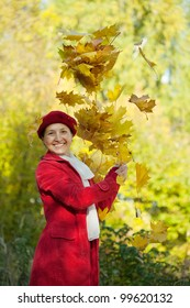 Happy mature woman throwing yellow maple leaves in the air in autumn