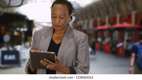 Happy mature woman using digital tablet outside near restaurant
