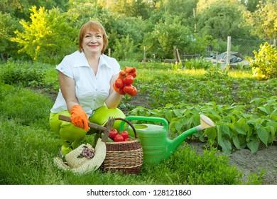 Happy mature woman in vegetables garden