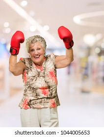 Happy Mature Woman Wearing Boxing Glove, Indoors