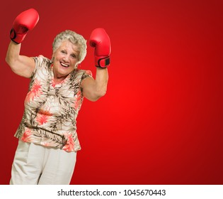 Happy Mature Woman Wearing Boxing Glove On Red Background