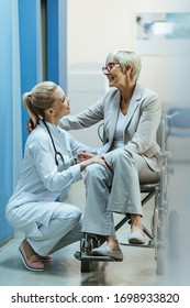 Happy mature woman in wheelchair talking to female doctor in a hallway at medical clinic.