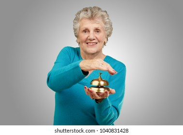 Happy Mature Woman While Holding Bell On Gray Background