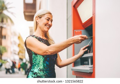 Happy mature woman withdraw money from bank cash machine with debit card - Senior female doing payment with credit card in ATM - Concept of business, banking account and lifestyle people