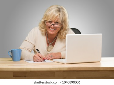 Happy Mature Woman Writing On Paper against a grey background