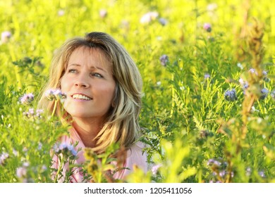 Happy mature women in flowerfield, close up