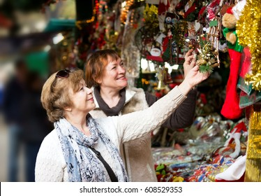 Happy mature women walking on the Christmas market and choosing jewelry