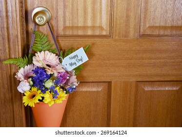 Happy May Day traditional gift of Spring flowers in orange cone hanging from door handle on wooden door.
