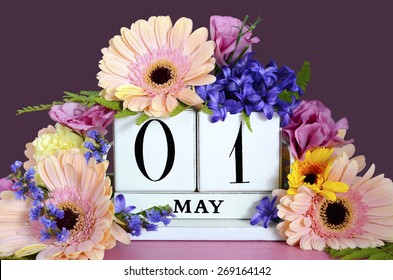 Happy May Day vintage wood calendar decorated with Spring flowers on pink wood table with dark purple background.