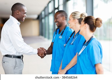 happy medical rep handshaking with group of doctors in hospital