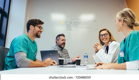 Happy medical team having a meeting in conference room in hospital. Doctors at briefing in hospital office.