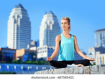 Happy meditating woman sitting in siddhasana yoga pose on city background