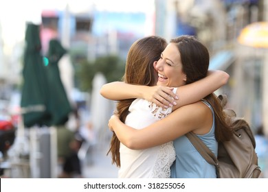 Happy meeting of two friends hugging in the street