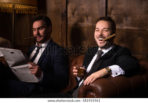 Happy men drinking whiskey and smoking cigars. Rich businessmen resting and relaxing in men's club. One man reading newspaper.
