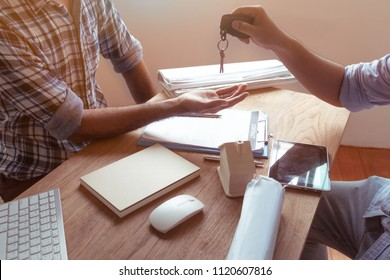 Happy men have been given the keys of their new home. Closeup from the hands of a real estate agent who gives a home key to a woman while her boyfriend signs a contract.