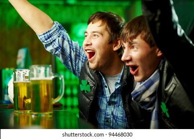 Happy men shouting while watching football match broadcast in pub