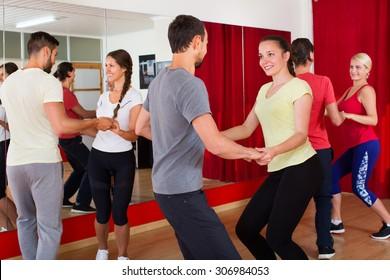 Happy men and women enjoying active dance at a dance studio