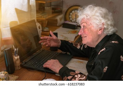 Happy merry grandmother learns to work at home on the computer and internet,