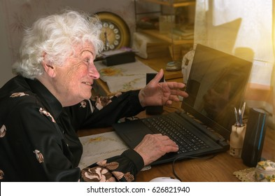 Happy merry grandmother learns to work at home on the computer and internet.