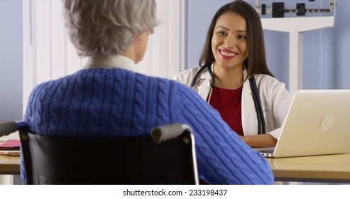 Happy Mexican doctor talking with senior patient