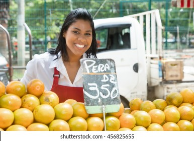 Happy mexican saleswoman with oranges on a farmers market