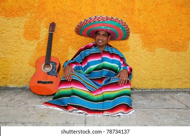 Happy mexican sit man typical sombrero hat colorful serape guitar