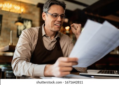 Happy mid adult barista analyzing paperwork while working in a pub.