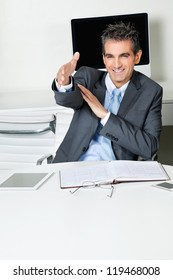 Happy mid adult businessman offering handshake while sitting at desk in office